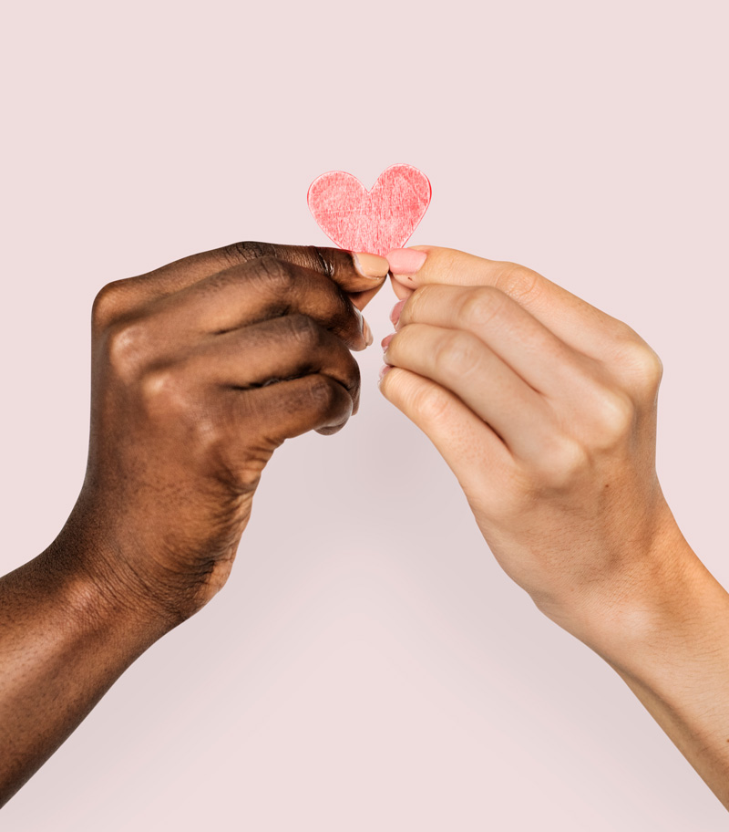 Bi-racial hands holding a paper heart together